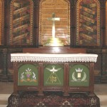 Altar frontal with (L) Communion bread and wine (M) the Holy Trinity and (R) Martyr's Symbols pre - 2009